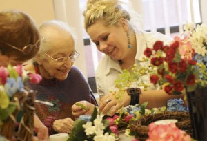 Marzena M'Barek of Chicago, director of the Oak Park Arms Adult Day Care, helps Esperanza Parrish of Oak Park